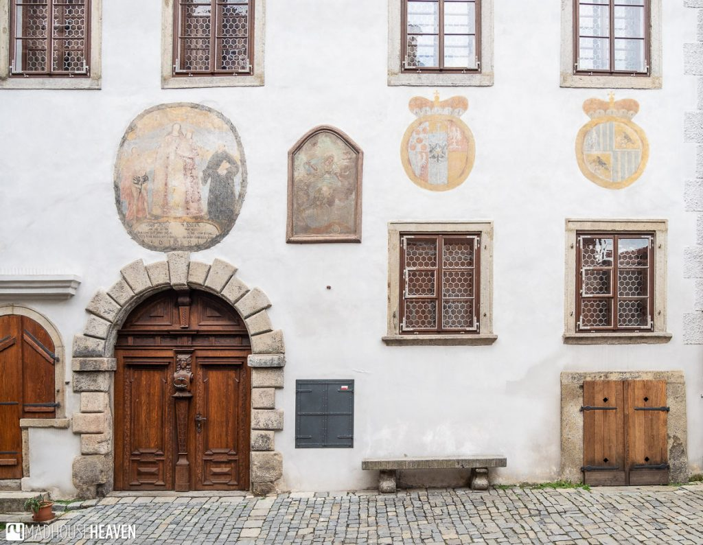 A faded Sgraffito painting of Jesus and several coats of arms on the side of a building in Cesky Krumlov