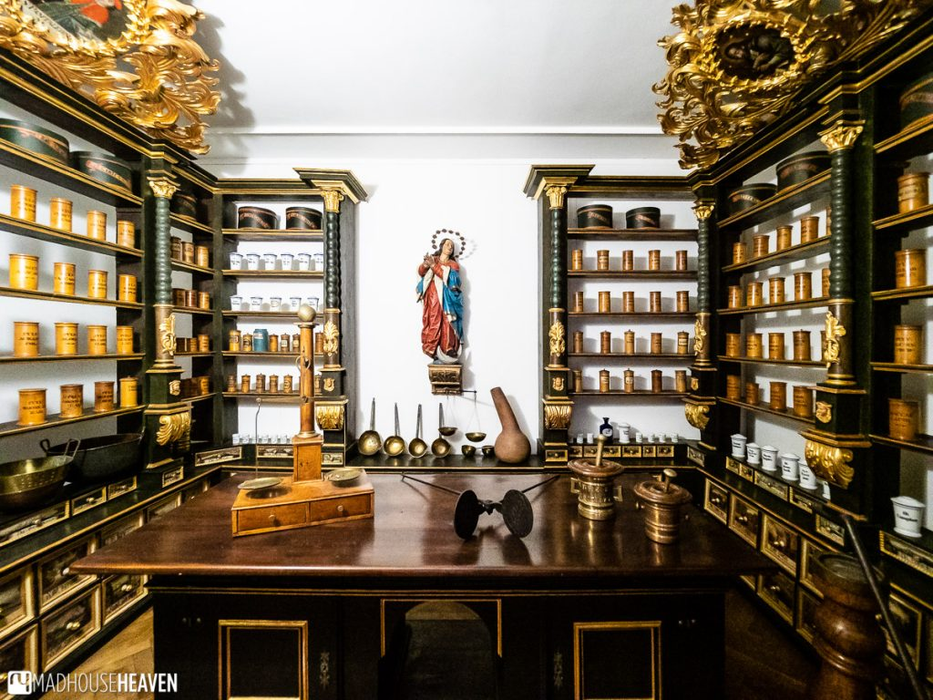 A renacment of a Czech pharmacy from the 1800s with a statue of the virgin mary on the wall