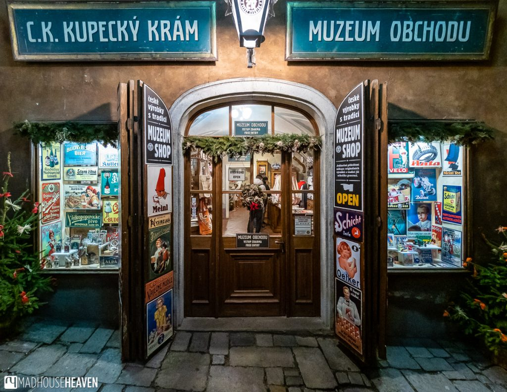 The entrance to Cesky Krumlov's Museum of Commerce - it has an art deco sign with decorated metal plates from the era entirely covering the door