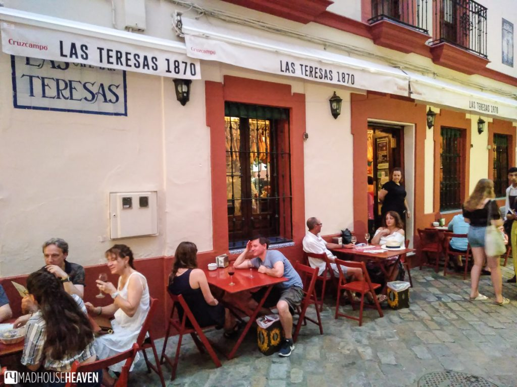 A restaurant terrace in Seville filled with patrons enjoying tapas and drinks