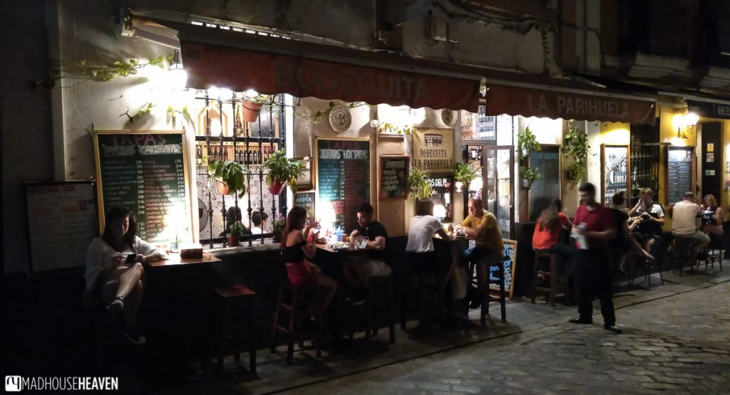 A brightly lit terrace with diners, on a night out in Seville