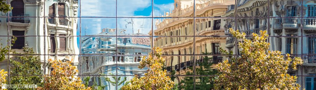 Colourful buildings in Granada reflected on the mirrored windows of a building