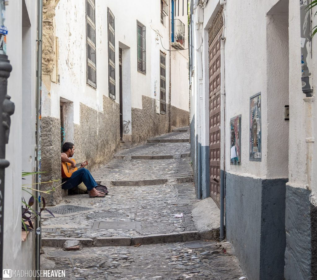 A guitarist playing music on the cobbled streets of Albaicín Granada