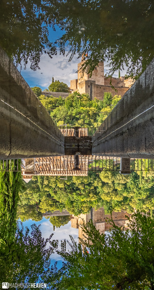 The fortress of Alhambra, reflected in a still pond shaded by trees
