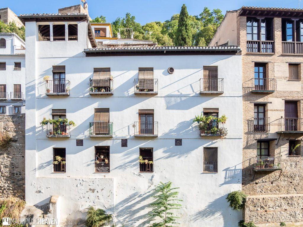 A white Spanish building in Granada along the river Darro that hosts La Tabernilla del Darro