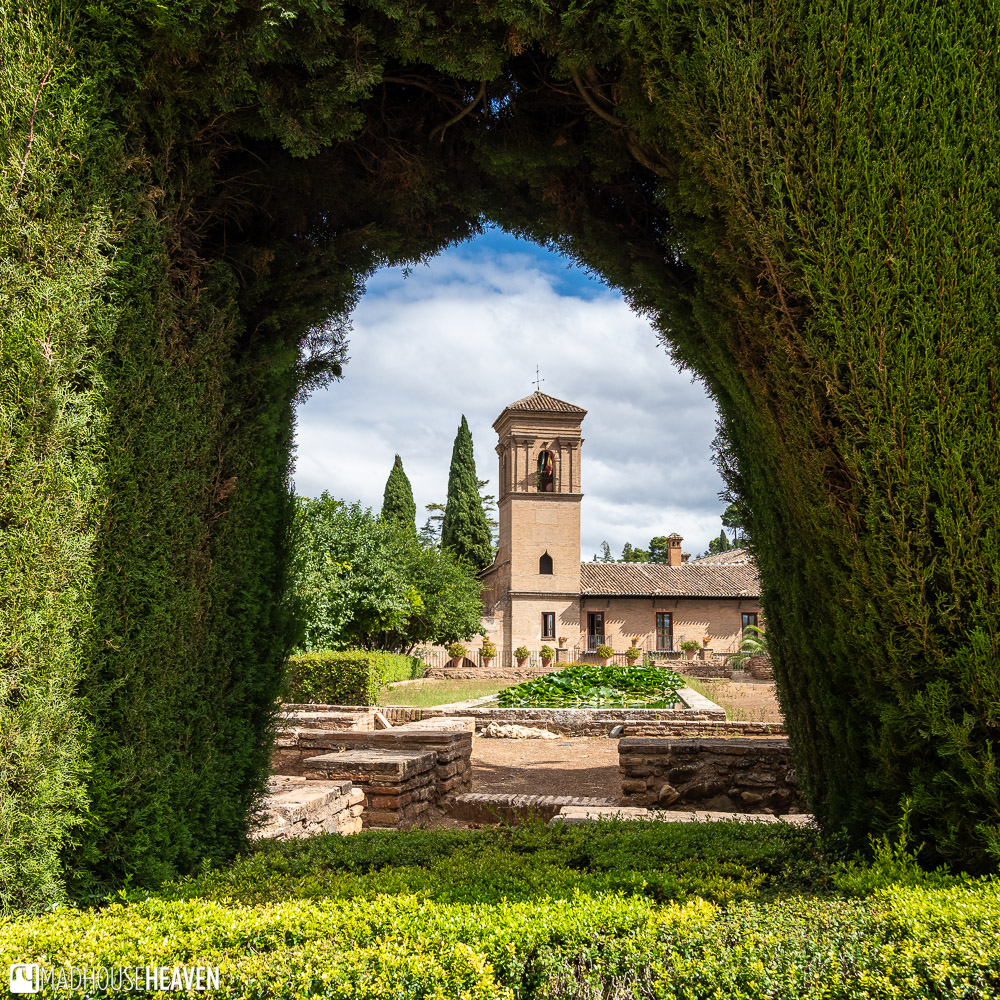 Parador de San Francisco seen through one of the windows in the hedges in the Calle Real de la Alhambra
