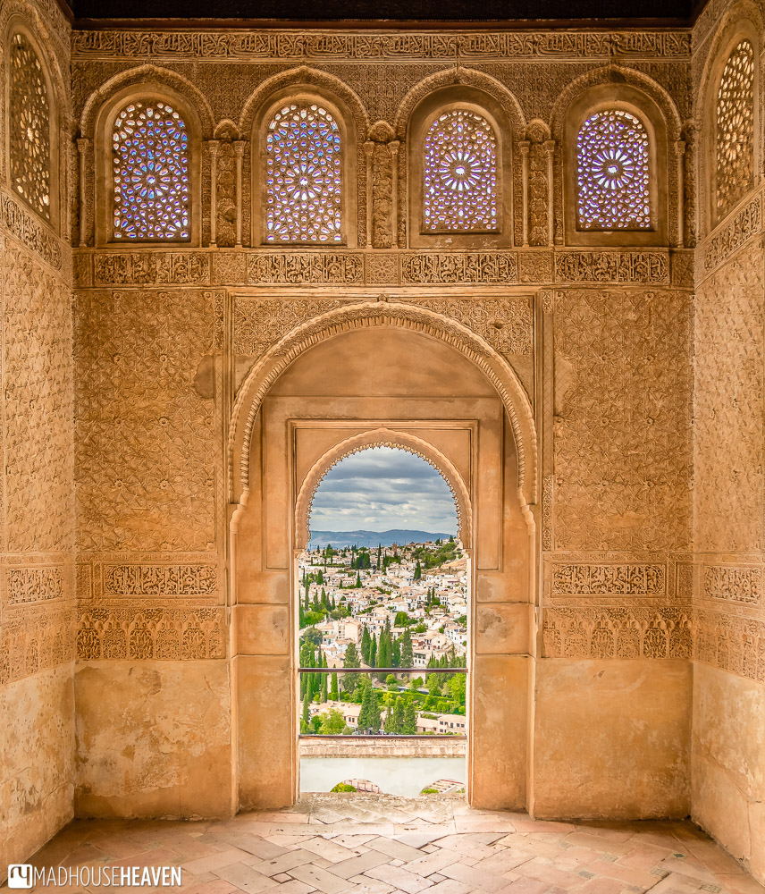 View of Granada through an arched doorway, from an elegant Moorish room with Islamic patterns covering its walls