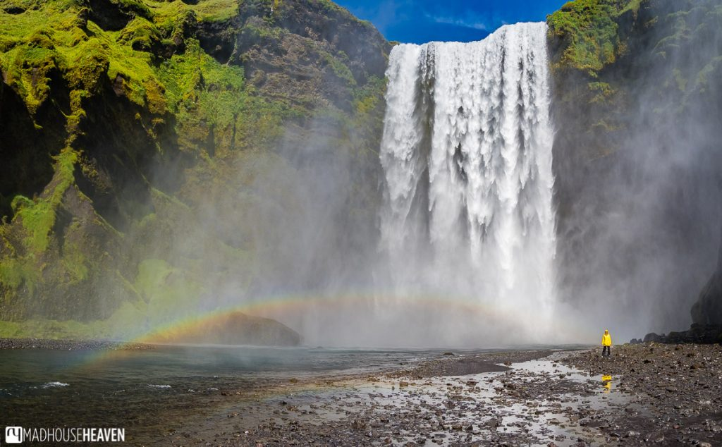 Panorama of the Skógafoss waterfall in Iceland, with a person in braght yellow jacket standing in front of it