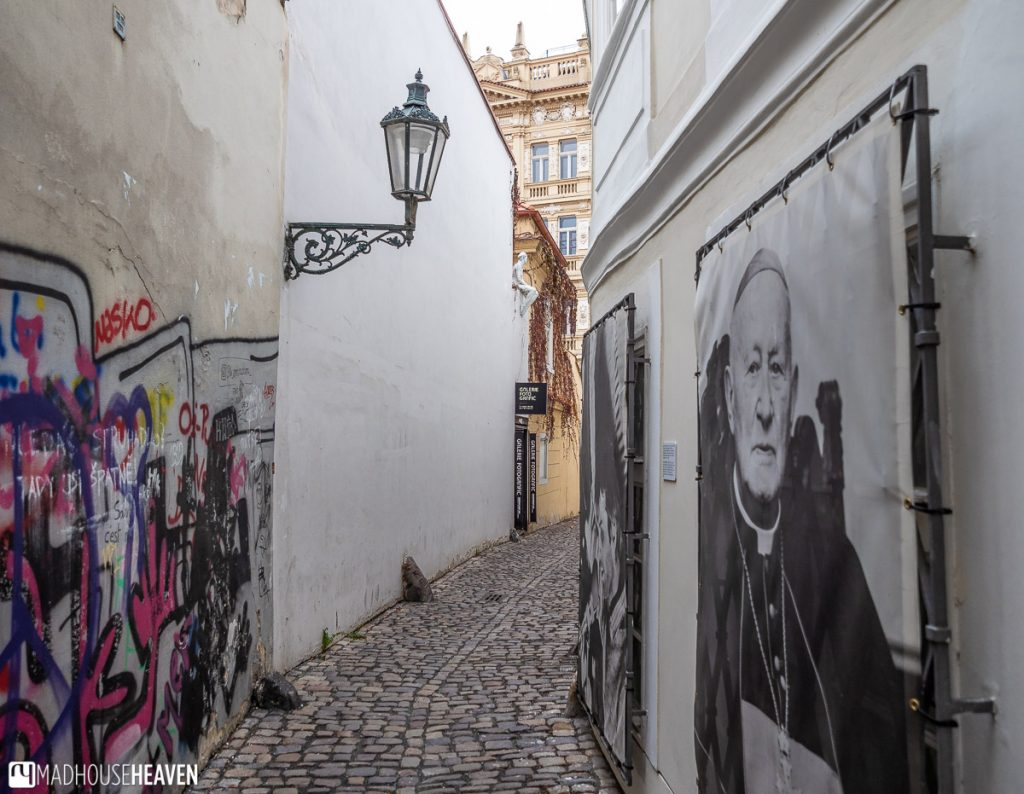 Black and white posters of Czech history from the 20th Century line the walls of Stříbrná alley