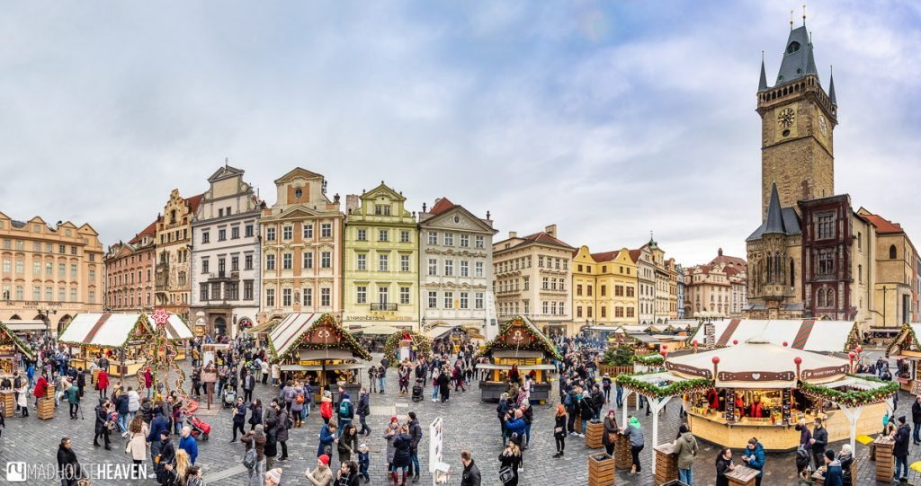 Cute colourful European buildings surrounding a Christmas market with the Old Town Hall and Astronomical clock of Prague on one side