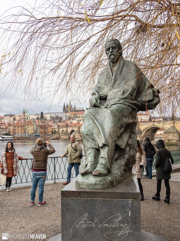 Statue of Czech composer Bedrich Smetana on a platform near Charles Bridge