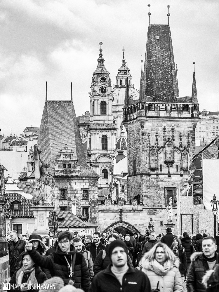 Charles Bridge packed with tourists tall and Gothic buildings rising out into the sky behind