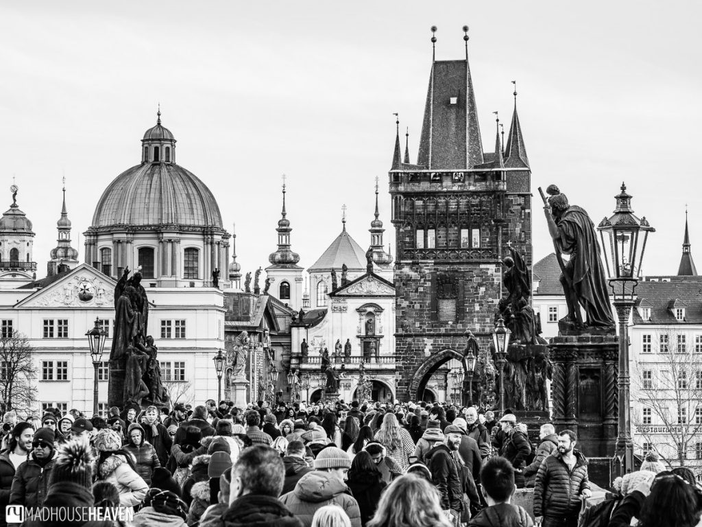 Black and white image of the Charles Bridge, with many people, statues, domes and towers of Prague in it