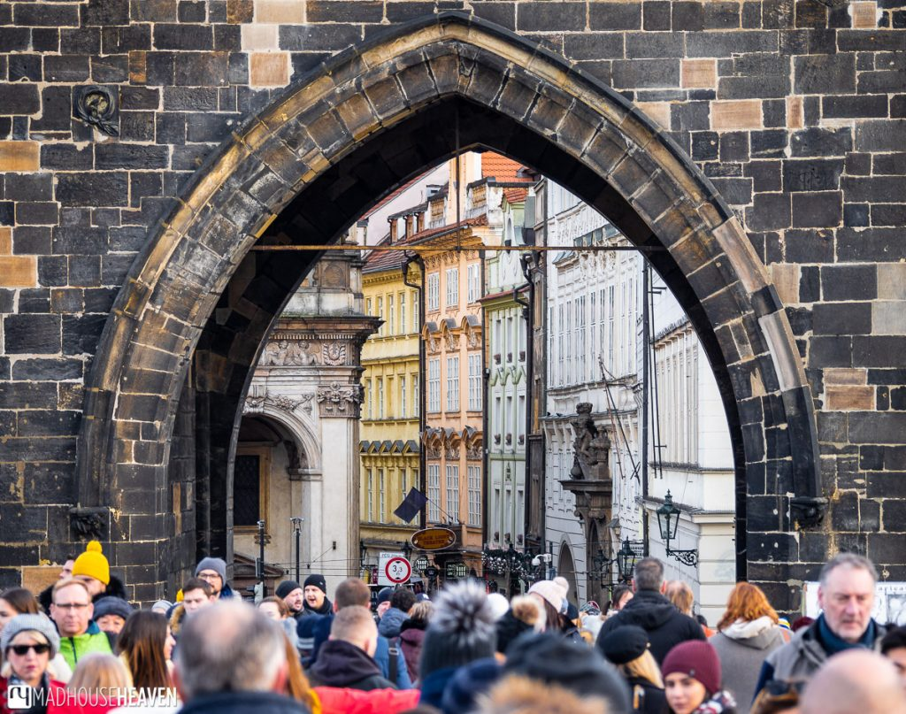 Looking under the arch of the Charles Bridge tower shows us a row of colourful Neo-Renaissance buildings curving off