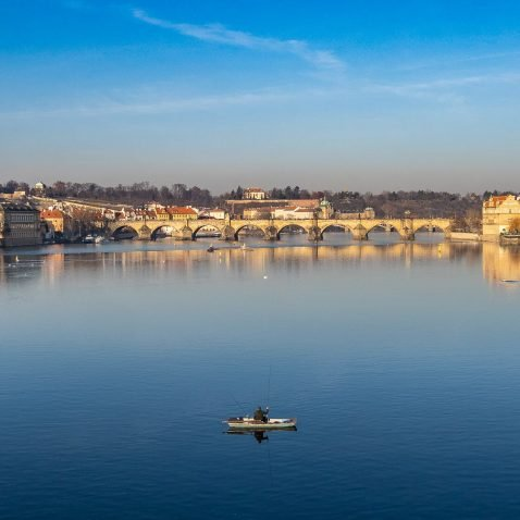 Man boating on the Vltava, overlooking Charles Bridge in Prague, the Czech Republic