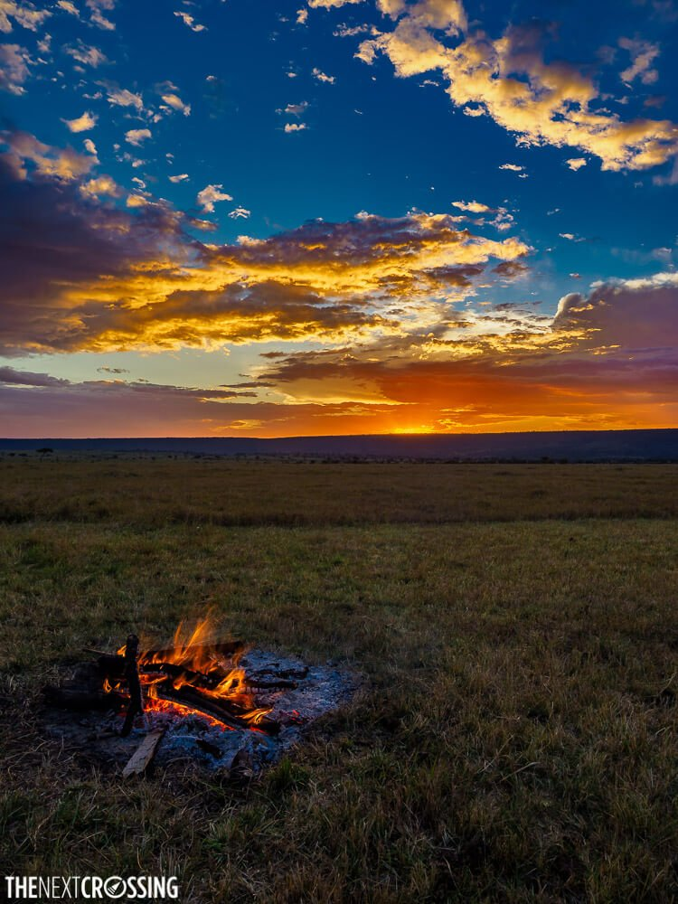 The orange glow of the campfire matches the blazing golden sunset above