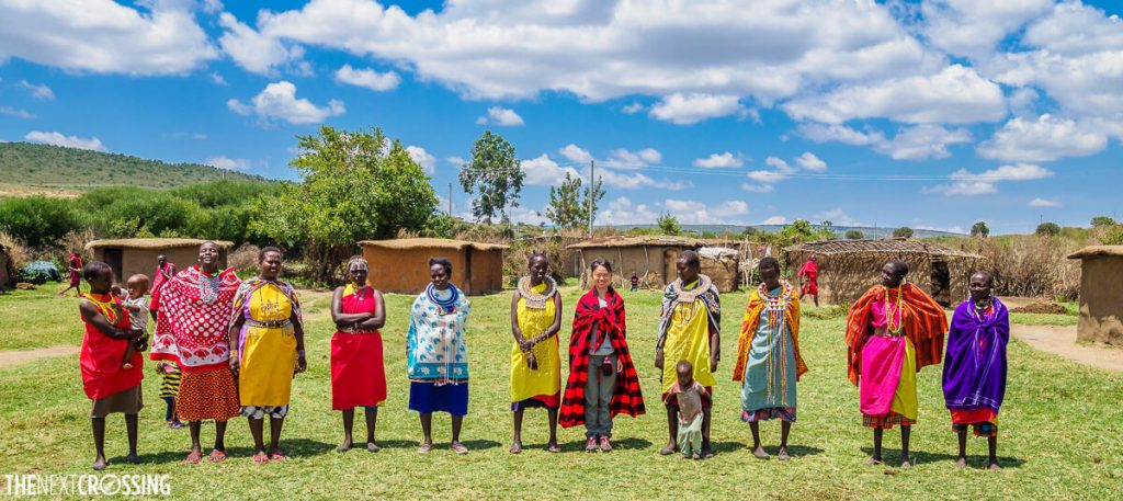 Maasai women dressed in colourful clothing in a village clearing