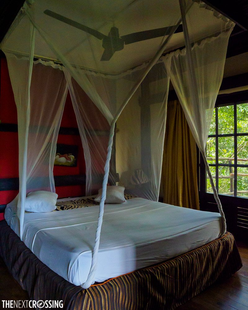 the bedroom with a four poster bed and mosquito net in shimba hill lodge