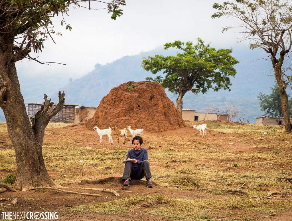 girl seated in front of large terminte mound in a Maasai village