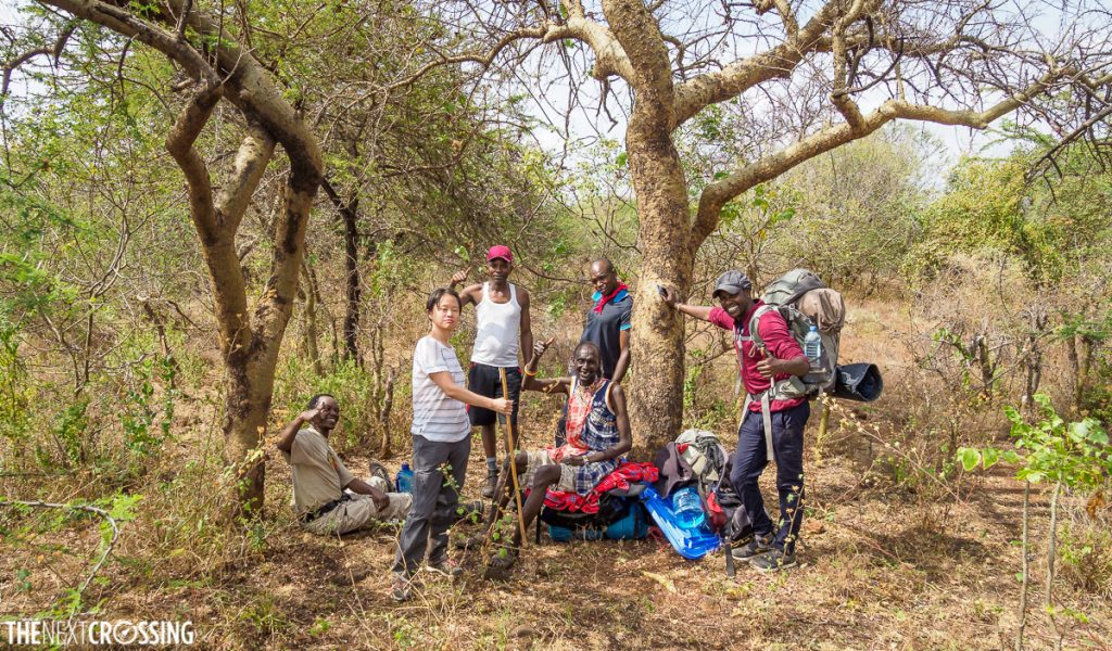 Kenyan guides, including Johnny, the Maasai, posing for a group photo in the dry african bush