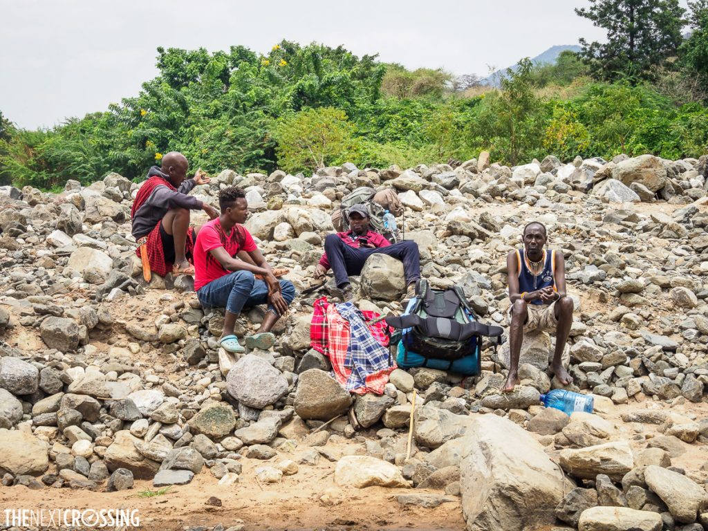 Kenyan guides sitting on the rocky bank of the Lenkutoto river