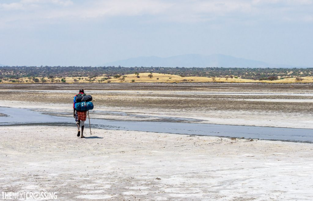 Maasai man with bags crossing the alkaline salt flats of the Magadi area