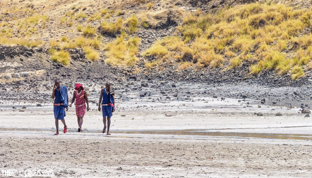 Maasai in colourful shukas crossing the partially flooded salt flats