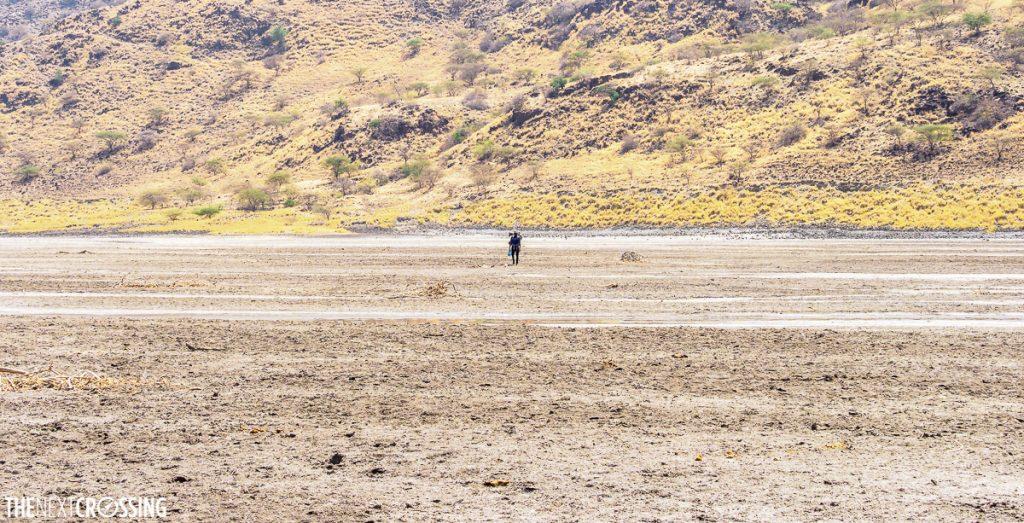 A kenyan man walking across the soda ash plains of lake magadi