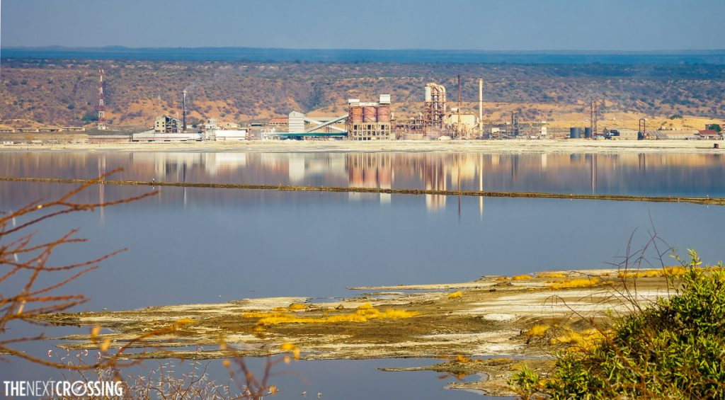 The lake magadi soda ash factory, an impressive industrial structure, reflected in the pearly alkaline waters of Lake Magadi