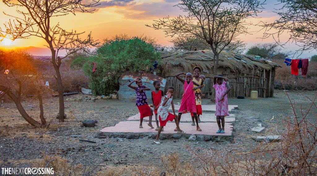Maasai children playing and posing for the camera in front of an African sunset